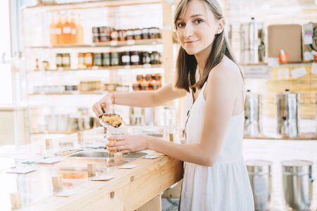 Bulk products in zero waste shop. Woman buying dry goods in plastic free grocery store. Girl with cotton bag and glass jars makes conscious shopping. Sustainable small businesses. Minimalist lifestyle