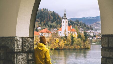 Travel Europe. Tourist person in yellow raincoat looking at Island with Church on Bled Lake in Slovenia. Girl in autumn or winter hiking outfit outdoor on nature. Freedom Adventure Lifestyle Concept. Standard-Bild - 133692610