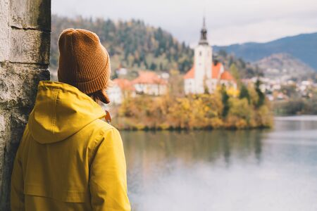 Travel Europe. Tourist person in yellow raincoat looking at Island with Church on Bled Lake in Slovenia. Girl in autumn or winter hiking outfit outdoor on nature. Freedom Adventure Lifestyle Concept. Standard-Bild - 133692710