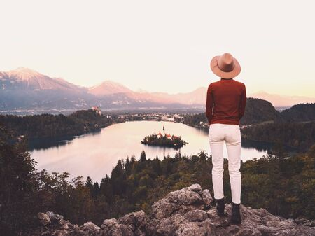 Travel Slovenia, Europe. Young woman looking at Bled Lake with Island, Castle and Alps Mountain. Calm meditate image of traveler people. Autumn or winter nature landscape. Vacation trip concept