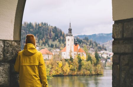 Travel Europe. Tourist person in yellow raincoat looking at Island with Church on Bled Lake in Slovenia. Girl in autumn or winter hiking outfit outdoor on nature. Freedom Adventure Lifestyle Concept. Standard-Bild - 133692717