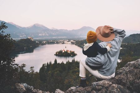 Journey Slovenia with kids. Family travel Europe. Mother with child looking on Bled Lake among nature and Alps mountains. Hiker woman in hat with backpack with her kids at autumn or winter vacation Reklamní fotografie