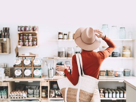 Minimalist vegan style girl with wicker bag and reusable glass coffee cup on background of interior of zero waste shop. Woman doing shopping without plastic packaging in plastic free grocery store.
