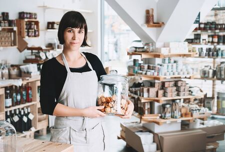 Small local business owner. Seller assistant with glass jar of pastries in interior of zero waste shop. Cheerful woman in apron stands behind counter with food products in plastic free grocery store.