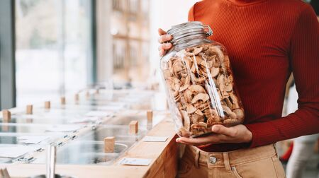 Concept of zero waste shop. Woman holding large glass jar with groceries on interior background of plastic free grocery store. Minimalist vegan style girl buying foods without plastic packaging.