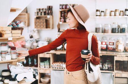 Jonge vrouw die producten kiest in een afvalvrije winkel. Meisje in minimalistische stijl met rieten tas die artikelen voor persoonlijke hygiëne koopt in plastic gratis winkel. Klant doet boodschappen zonder plastic verpakking.