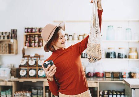 Jeune femme de style végétalien minimaliste avec un sac en filet réutilisable en coton et une tasse à café en verre réutilisable sur fond de marchandises du magasin zéro déchet. Achats sans emballage en plastique dans un magasin sans plastique.