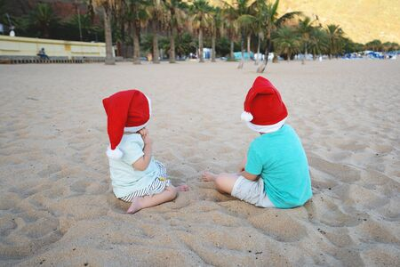 Boy and girl in red santa hats having fun on ocean sand beach. Kids playing on sea coast background. New Year or Merry Christmas, winter vacation in warm countries. Family holiday on Tenerife, Spain.