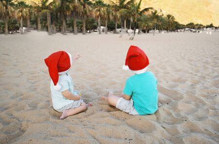 Boy and girl in red santa hats having fun on ocean sand beach. Kids playing on sea coast background. New Year or Merry Christmas, winter vacation in warm countries. Family holiday on Tenerife, Spain. Stockfoto - 134621217
