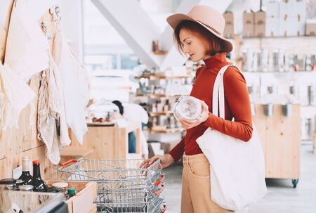 Young woman with reusable cotton bag and empty jar doing shopping in plastic free store. Minimalist vegan style girl buying groceries without plastic packaging in zero waste shop. Low waste lifestyle. Фото со стока