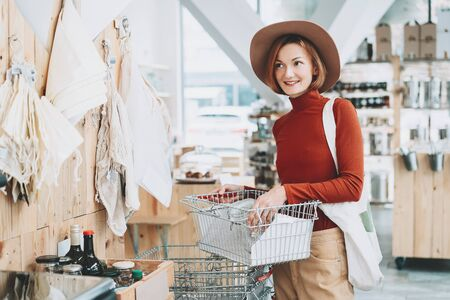 Young woman with reusable cotton bag and empty jar doing shopping in plastic free store. Minimalist vegan style girl buying groceries without plastic packaging in zero waste shop. Low waste lifestyle. Reklamní fotografie