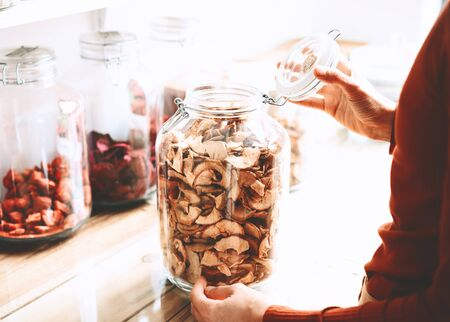 Woman choosing dried berries and fruits in glass jars in zero waste shop. Sustainable shopping in plastic free grocery store. Minimalist vegan style young girl buying foods without plastic packaging