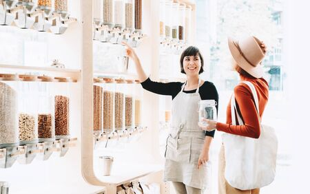 Shop assistant helping customer in bulk food store. Seller advising woman in her purchase of groceries without plastic packaging in zero waste shop. Sustainable shopping at small local businesses. Reklamní fotografie