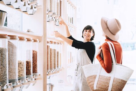 Shop assistant helping customer in bulk food store. Seller advising woman in her purchase of groceries without plastic packaging in zero waste shop. Sustainable shopping at small local businesses.
