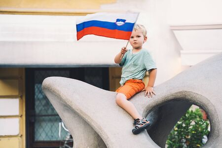 Child holding slovenian flag in hands on the background of urban architecture of Ljubljana, Slovenia, Europe.