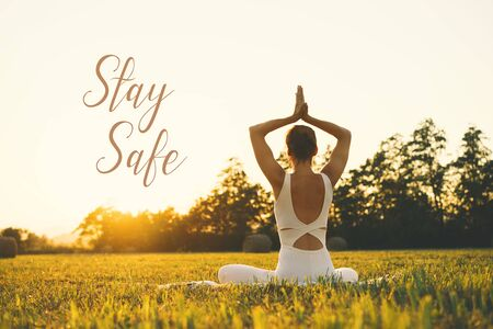 Yoga Girl. Young woman doing yoga and meditation on nature. Concept image of quarantine message, motivation quote across the globe to fight COVID-19 pandemic with text Stay Safe. Stockfoto