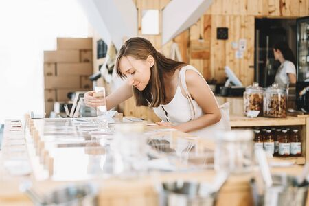 Beautiful girl with cotton bag and glass jars makes conscious shopping in zero waste shop. Woman buying dry goods in plastic free grocery store. Sustainable small businesses. Minimalist lifestyle. Reklamní fotografie
