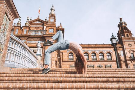 Beautiful woman in yoga pose - Upward Bow or Wheel Pose - on bridge of Plaza de Espana in Seville, Andalusia, Spain. Casual young tourist girl doing yoga in european historical city. Travel Europe. Imagens