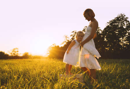 Young pregnant woman with child outdoors in meadow in sunlight at sunset. Mother and daughter on nature. Little girl with her mom, who pregnant for second time. Health pregnancy, family background.