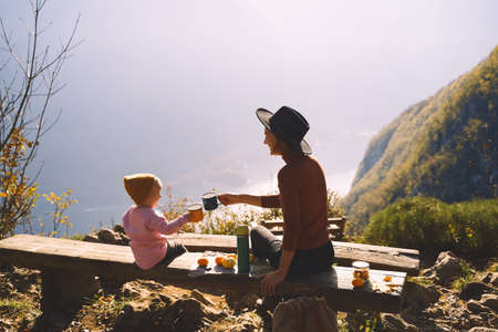 Beautiful happy family outdoors. Mother and daughter on a picnic in mountains. Mom and child girl holding enameled tourists mugs of hot tea. Adventure travel with kids, camping and hiking in nature. Foto de archivo