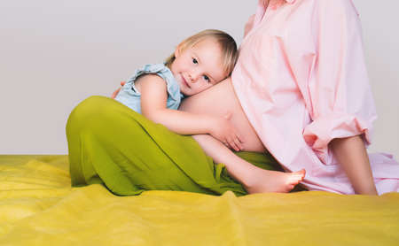 Pregnant mother and daughter together at home. Woman with her first child during second pregnancy. Motherhood and parenting concept. Toddler smiling girl and mom. Happy family expecting for new baby.