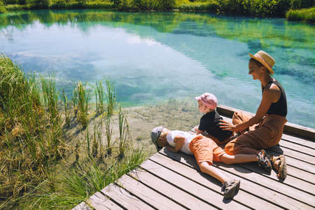 Family of tourists in nature. Young woman with little kids on wooden bridge in green nature background. Mother and child together. Adventure travel Slovenia, Europe.