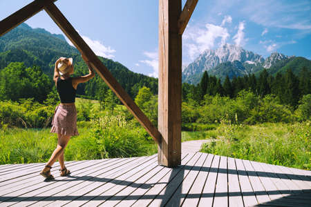Travel, Freedom, Lifestyle concept. Young woman enjoying green nature outdoors. Amazing view on Zelenci (into English means - green) natural reserve in Slovenia, Europe. People in nature background.