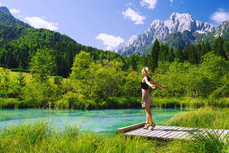 People in nature. Tourist woman with raised arms up in green nature background. View on Zelenci (into English means - green) natural reserve in Slovenia, Europe. Travel, Freedom, Lifestyle concept. 스톡 콘텐츠