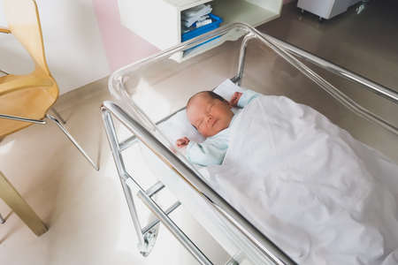 Newborn baby is sleeping in small transparent portable plastic bed. Baby first days of life is lying in a hospital crib after birth.