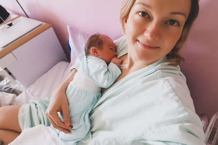 Mother and newborn resting after childbirth in maternity hospital room. Mother hugging her sleeping newborn baby.