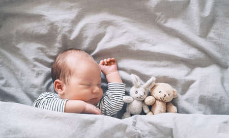 Newborn baby sleep at first days of life. Portrait of new born child boy one week old sleeping peacefully with a cute soft toy in crib in cloth background.