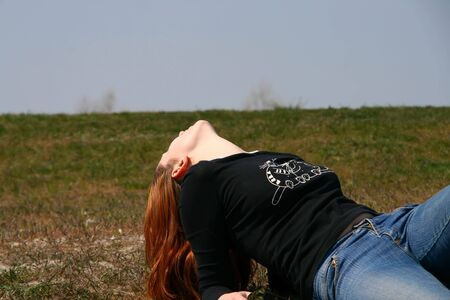 unrecognizable: the girl lying on the grass exposing her chin to the sun Stock Photo