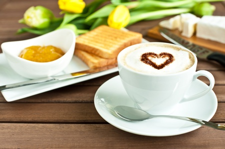 Cup of coffee with heart, mango jam, cheese and yellow tulips photo
