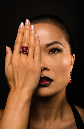 Beautiful fashion asian woman portrait with accessories- earrings and ring. Imagens