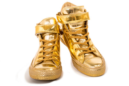Pair of golden sneakers isolated