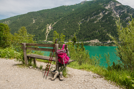 Hanging backpack and hiking shoes. Hiking path. Achensee, Austria
