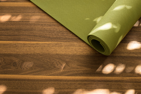 Yoga mat on a wooden background. Equipment for yoga. Concept healthy lifestyle. Lots of copyspace