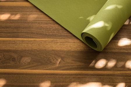 Yoga-Matte auf einem hölzernen Hintergrund. Die Ausrüstung für Yoga. Konzept gesunde Lebensweise. Viele Exemplar