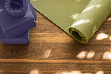 Yoga mat on wooden floor in evening light with shadows from window Imagens