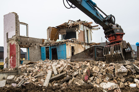 Heavy construction machines demolishing an old house
