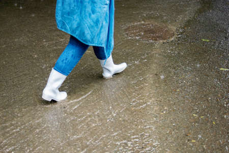 A woman in white rubber boots walks down the street in the rain. Water flows along the road. Street scenes in the rain. Rainy fall weather.