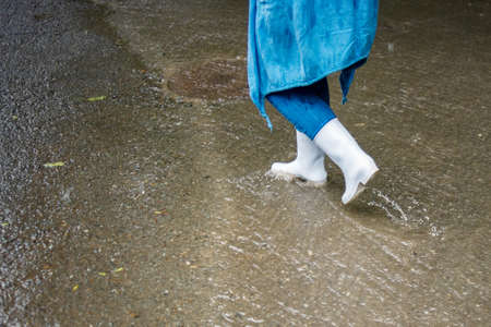 A woman in white rubber boots walks down the street in the rain. Water flows along the road. Street scenes in the rain. Rainy autumn weather.