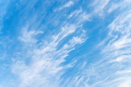 Blue sky and white cirrus clouds background. Amazing spindrift clouds. Natural cloudy backdrop.
