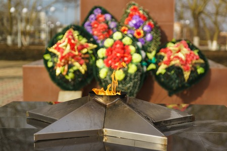 The eternal flame on the background of the assigned wreaths of memory Stock Photo