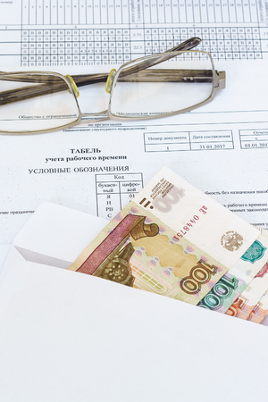 Glasses and an envelope with ruble bills lying on the sheet of accounting of working time. Payroll. Russia Stock Photo