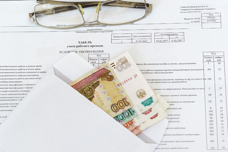 earned: Glasses and an envelope with ruble bills lying on the sheet of accounting of working time. The calculation of remuneration. Russia
