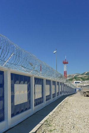 Beautiful white and blue concrete fence with barbed wire in the industrial area of Novorossiysk city