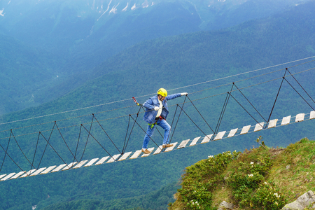 An elderly man in a denim suit, helmet, and rescue ropes is a rope bridge high in the mountains. Cloudy summer day Stock Photo