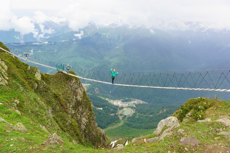 ski walking: Estosadok, Sochi, Russia - June 10.2017: Three tourists walking on a rope bridge stretched over the gorge to the ski resort Rosa Khutor. Cloudy summer day