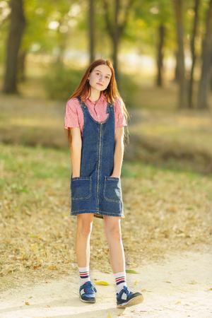 Succès heureux belle adolescente aux cheveux longs dans une robe d'été en jean avec un sourire dans le parc